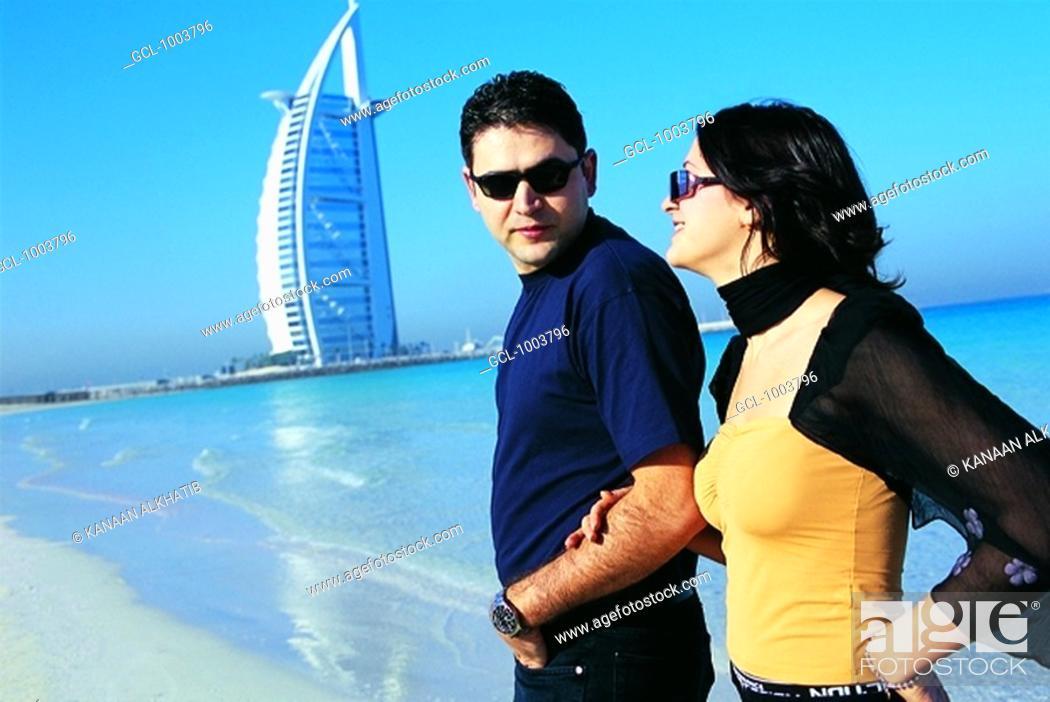 Stock Photo: Western couple on the beach near Burj Al Arab hotel in Dubai, UAE.