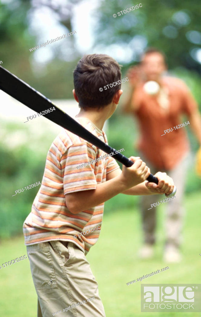 Stock Photo: Father and son playing baseball in garden (10-11).