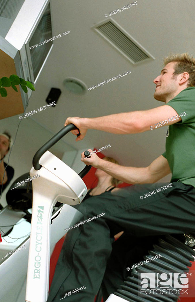 Stock Photo: Young man at the fitness studio, gym, working out, doing exercises, cycling.