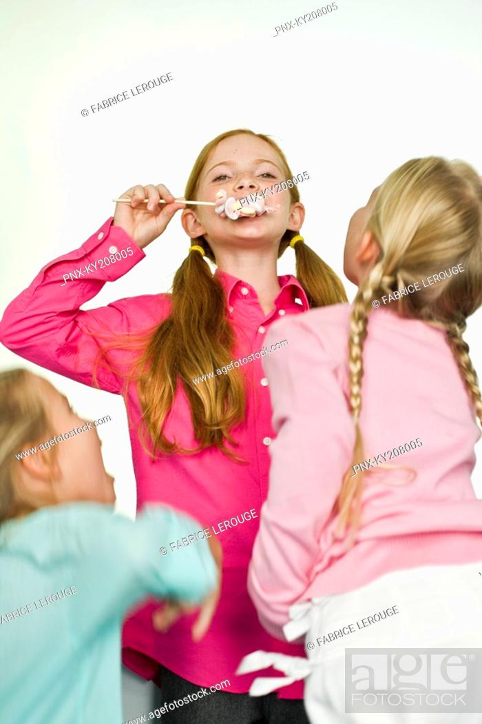 Stock Photo: Girl eating a lollipop and her friends looking at her.