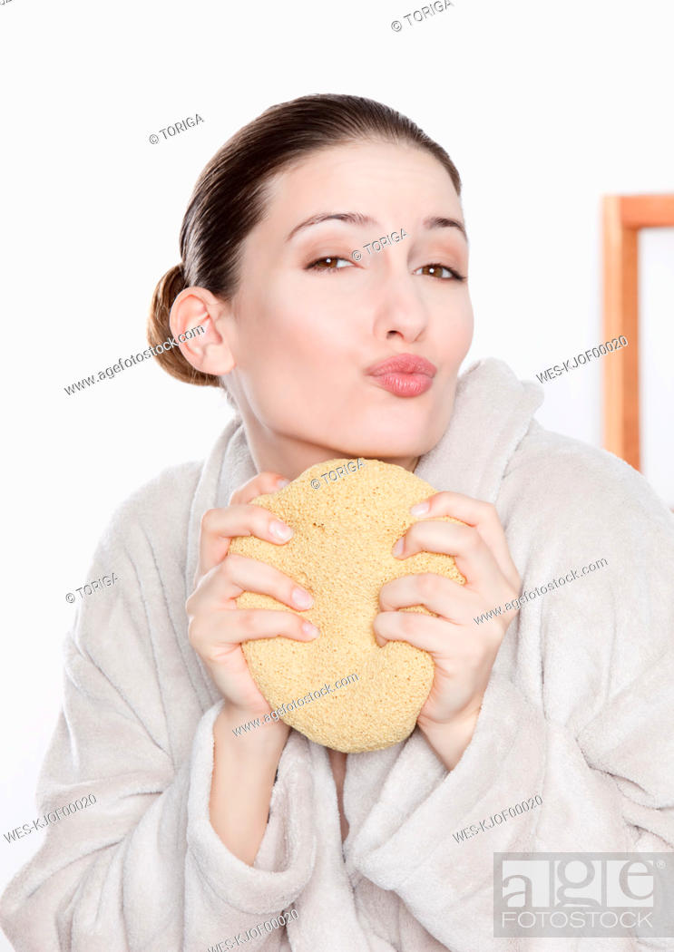 Stock Photo: Woman in bathrobe holding sponge and pouting, portrait.