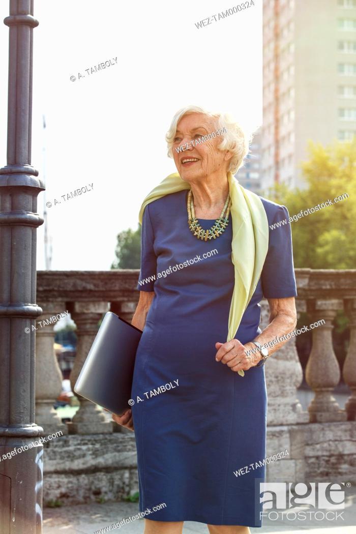 Stock Photo: Germany, Berlin, portrait of senior woman carrying laptop.