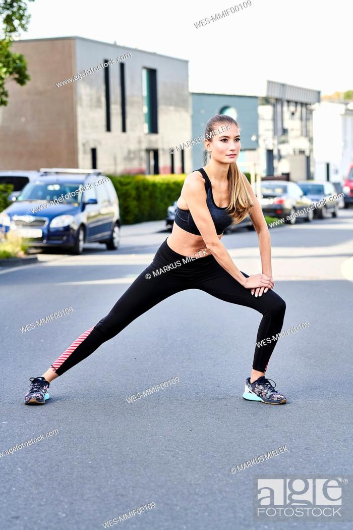 Photo de stock: Sportive young woman stretching on a street in the city.