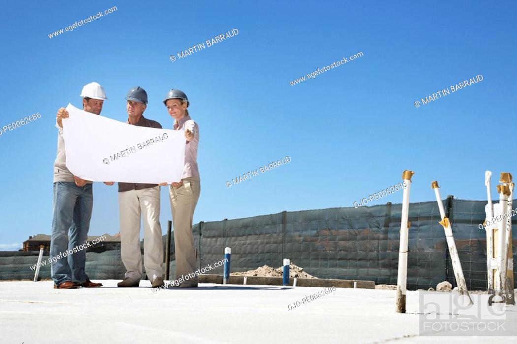 Stock Photo: Architect viewing blueprints with home owners.
