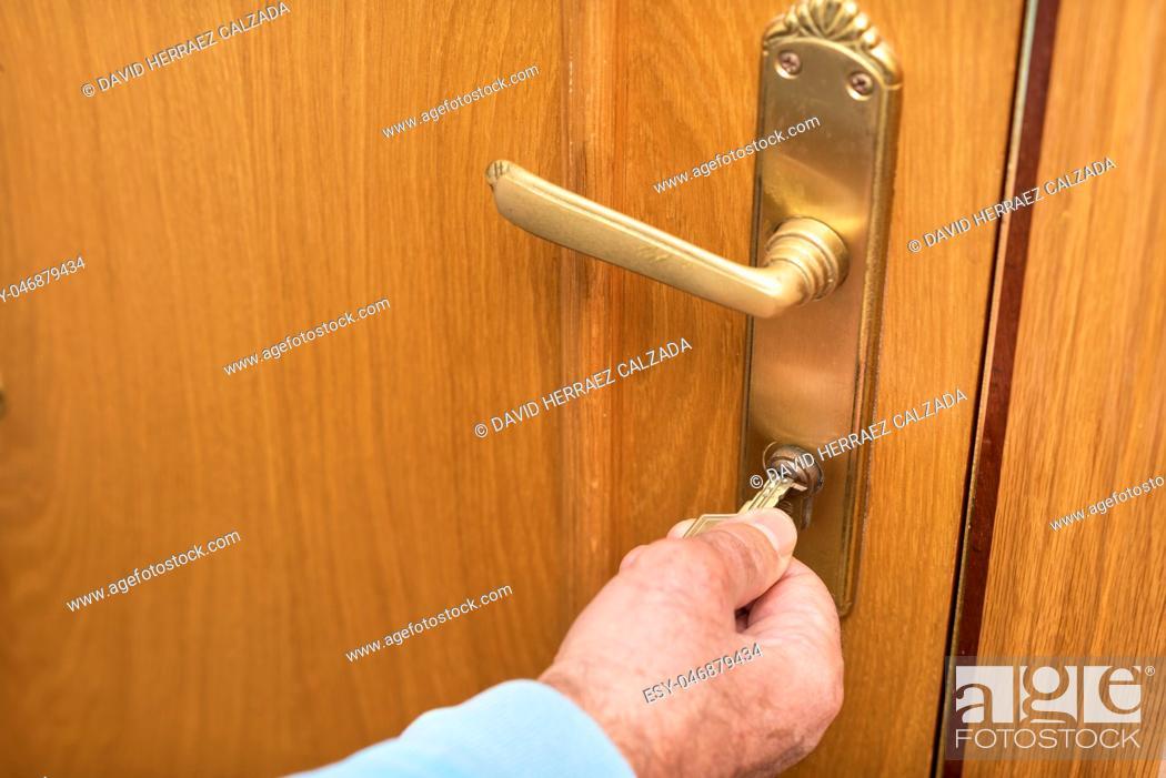 Photo de stock: Senior man Locking up door with key in hand.