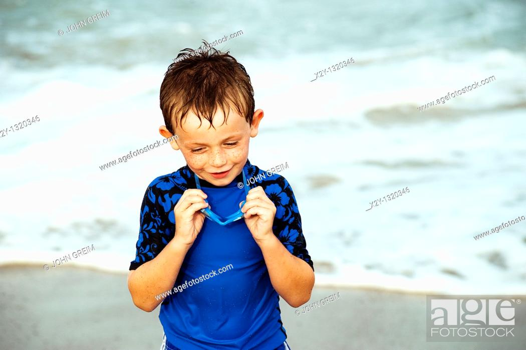 Stock Photo: Young boy with goggles enjoys the ocean water.