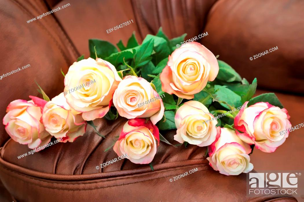Stock Photo: Still life : on the leather brown chair lay a bouquet of beautiful roses.