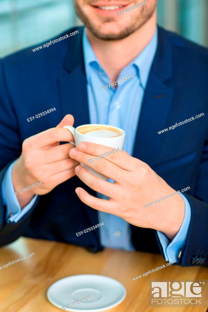 Stock Photo: Close-up shot with selective focus of good-looking smiling man holding a cup of coffee.
