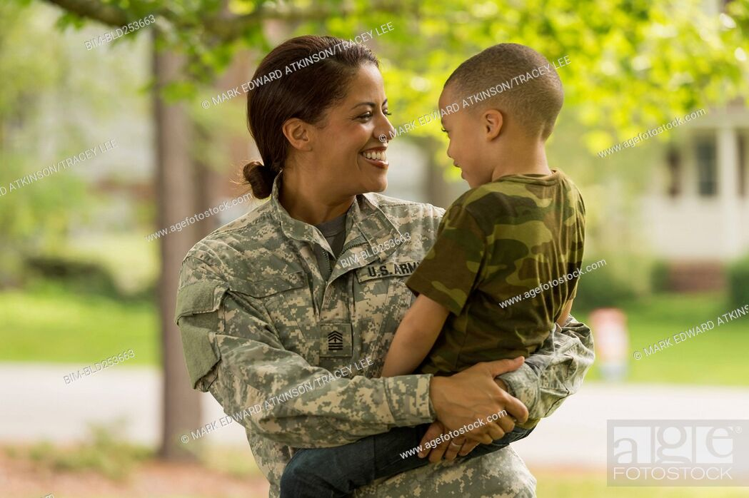 Stock Photo: African American soldier mother carrying son.