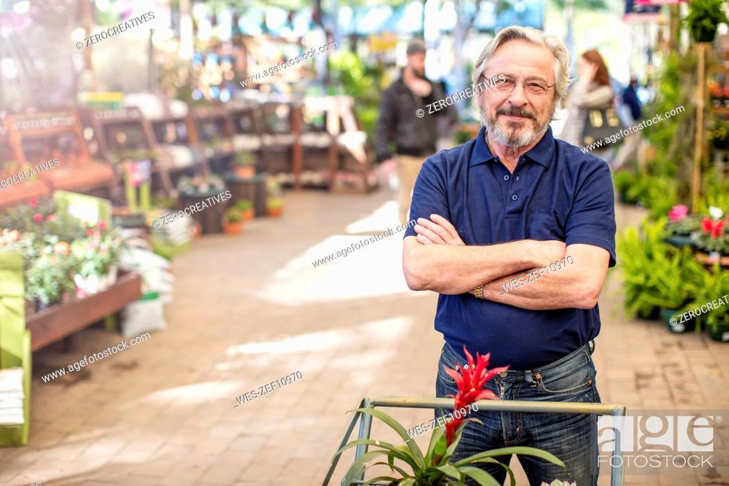 Stock Photo: Senior man shopping for plants at garden centre.