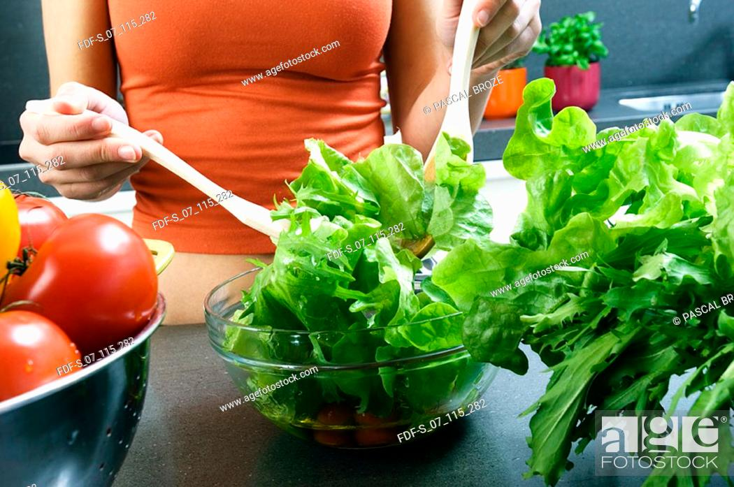 Stock Photo: Mid section view of a woman preparing salad.