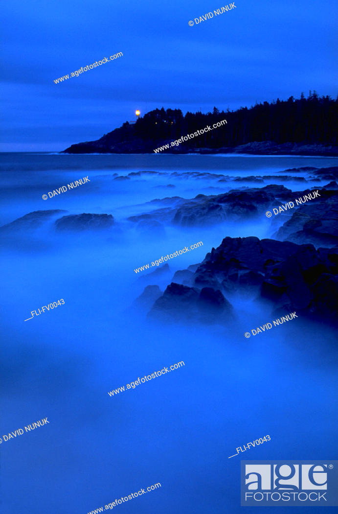 Stock Photo: Coastline at dusk with lighthouse in background.