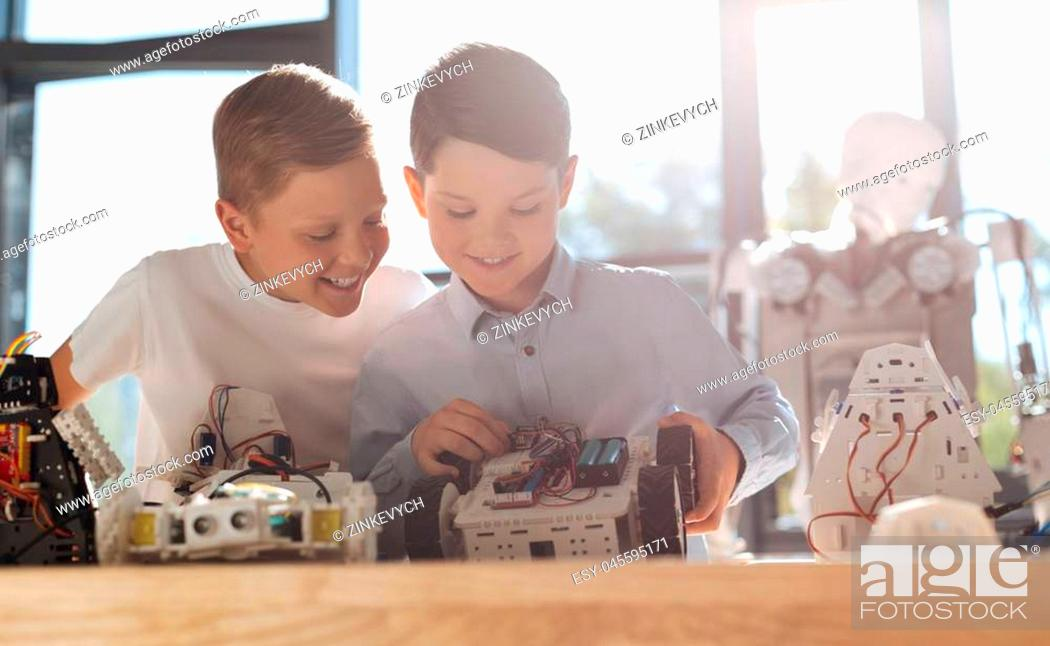 Stock Photo: Curious look. Merry smiling little boy sitting at the table next to his friend constructing a robotic vehicle and looking at his work with curiosity.