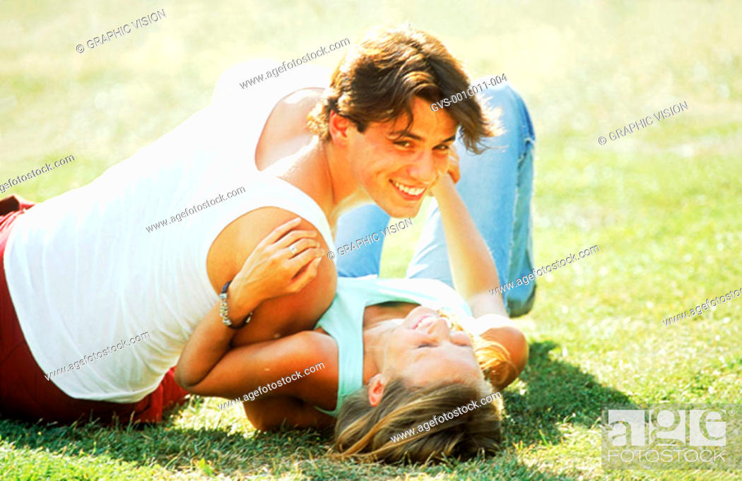 Stock Photo: Young couple lying on a lawn.