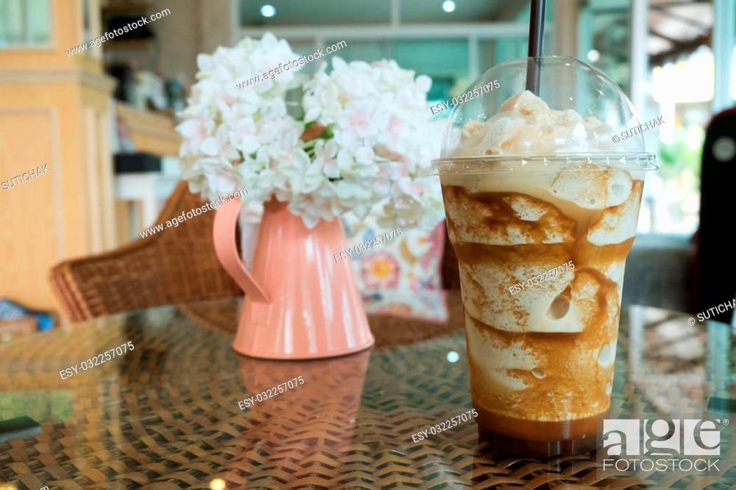 Stock Photo: iced frappe coffee in plastic mug put on the rattan weave table in coffee shop cafe.