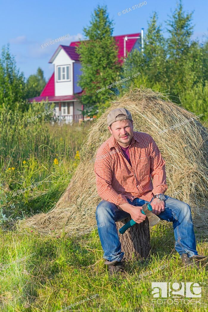 Stock Photo: Farmer with an axe on haystack on background.