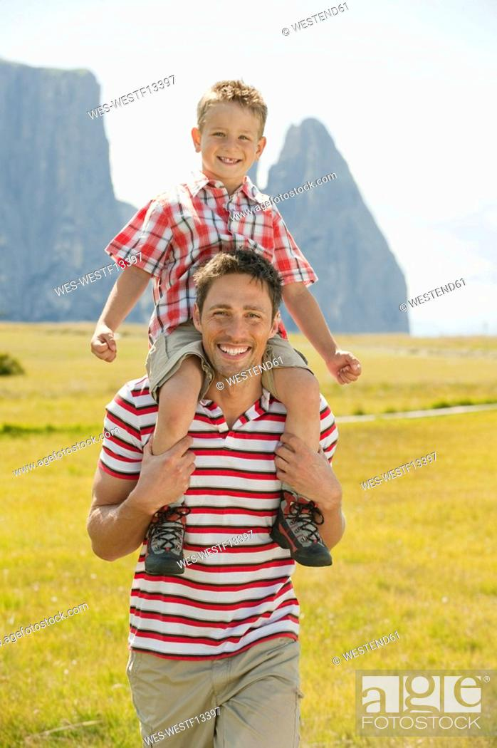 Stock Photo: Italy, Seiseralm, Fahter carrying son 6-7 on his shoulder, smiling, portrait.