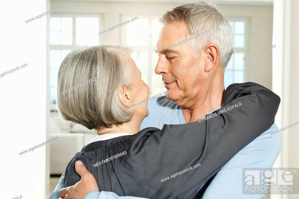 Stock Photo: Germany, Berlin, Senior couple embracing, smiling.
