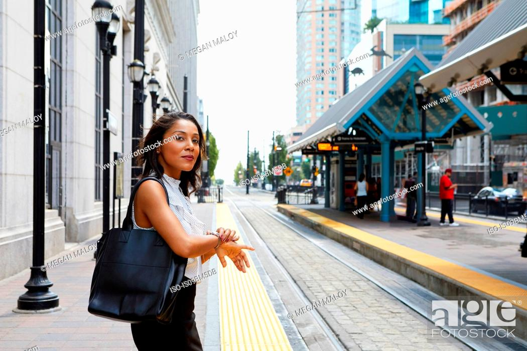 Imagen: Businesswoman checking time by light rail line.