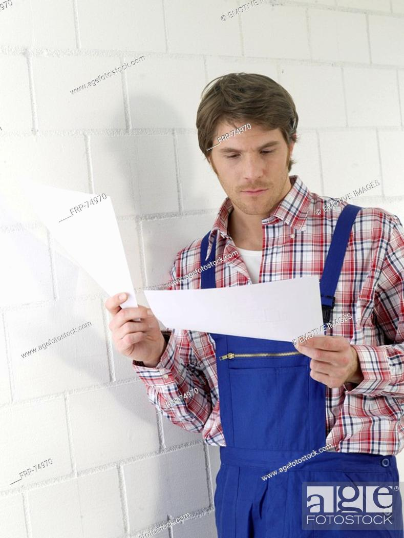 Stock Photo: Mann wearing work wear holding contruction plans.