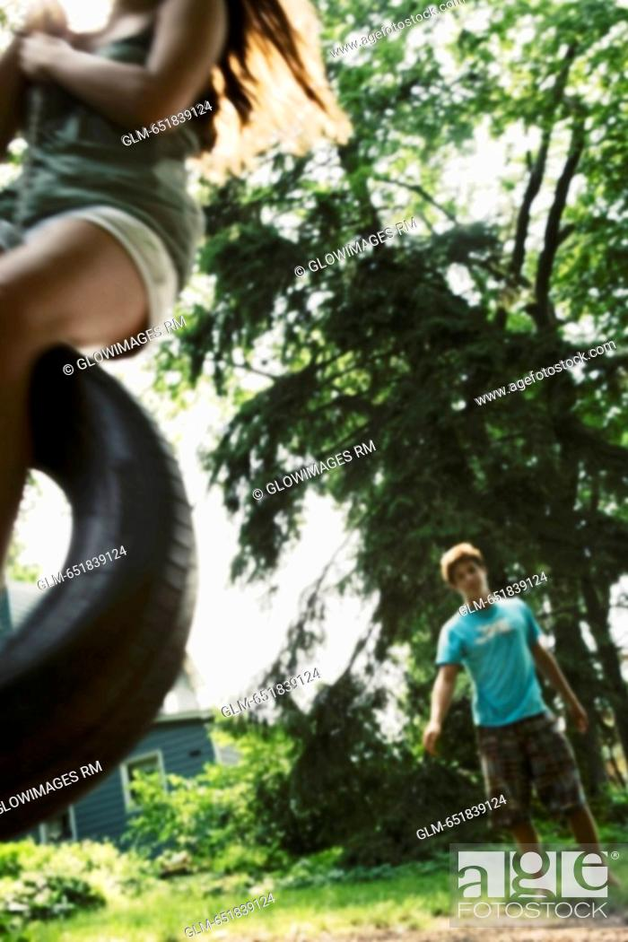 Stock Photo: Teenage girl swinging on a tire swing with a young man in the