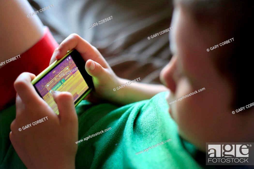 Stock Photo: An 8 year old boy playing a game on an IPod or smartphone.