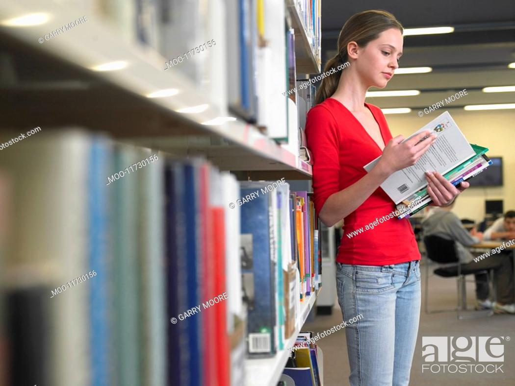 Stock Photo: Teenage student reading text books by library shelf.