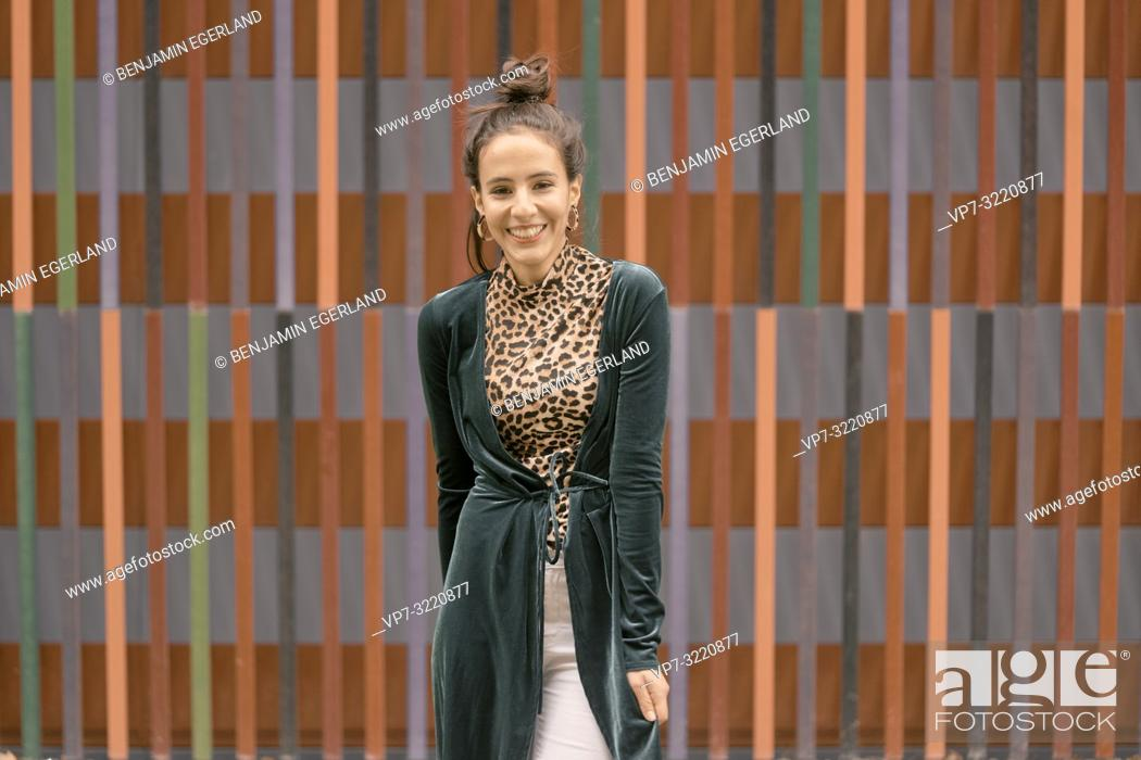 Stock Photo: fashionable woman laughing candid in front of geometrical line pattern, in Munich, Germany.