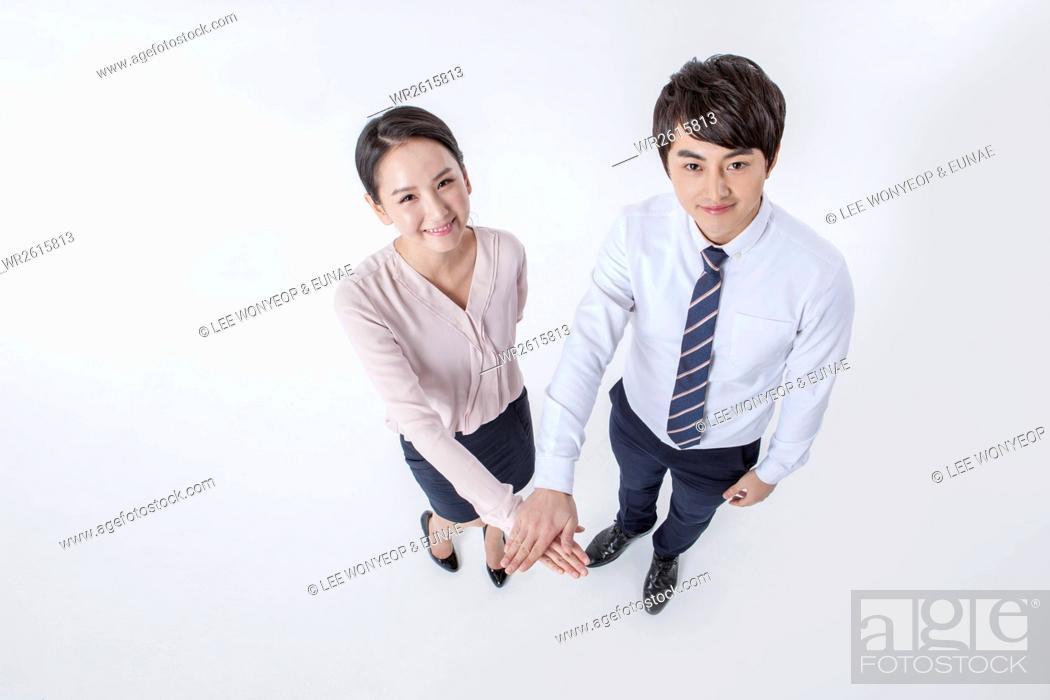 Imagen: Smiling business people holding hands.