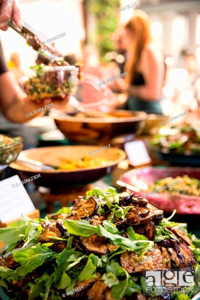 Stock Photo: Serving eggplant salad at cooperative food market stall.