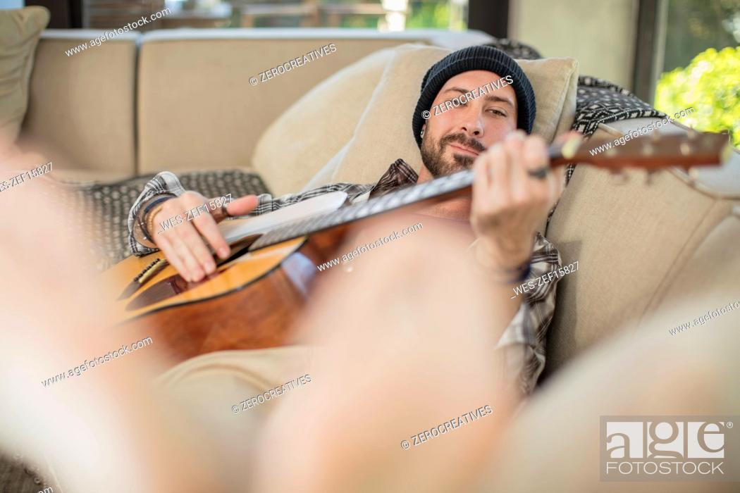 Imagen: Young man at home lying on couch playing guitar.