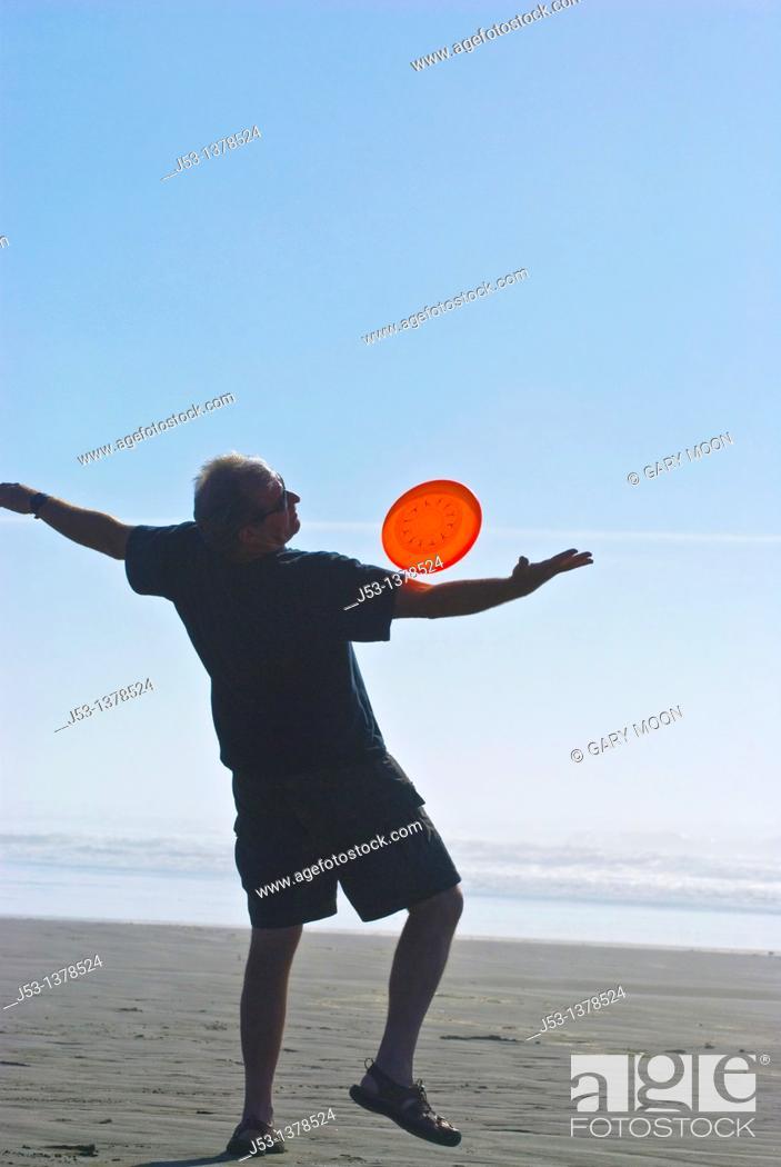 Stock Photo: Man playing freestyle frisbee on California beach.