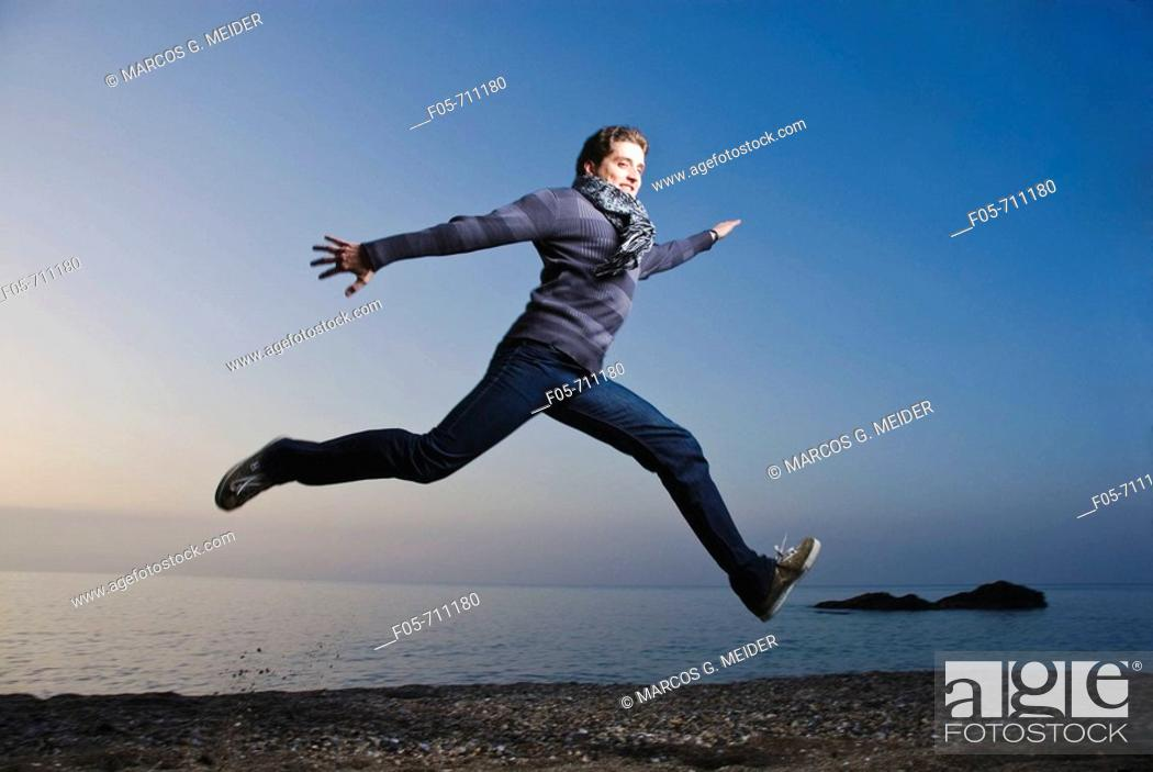 Stock Photo: Young man jumping along the seashore at dawn.