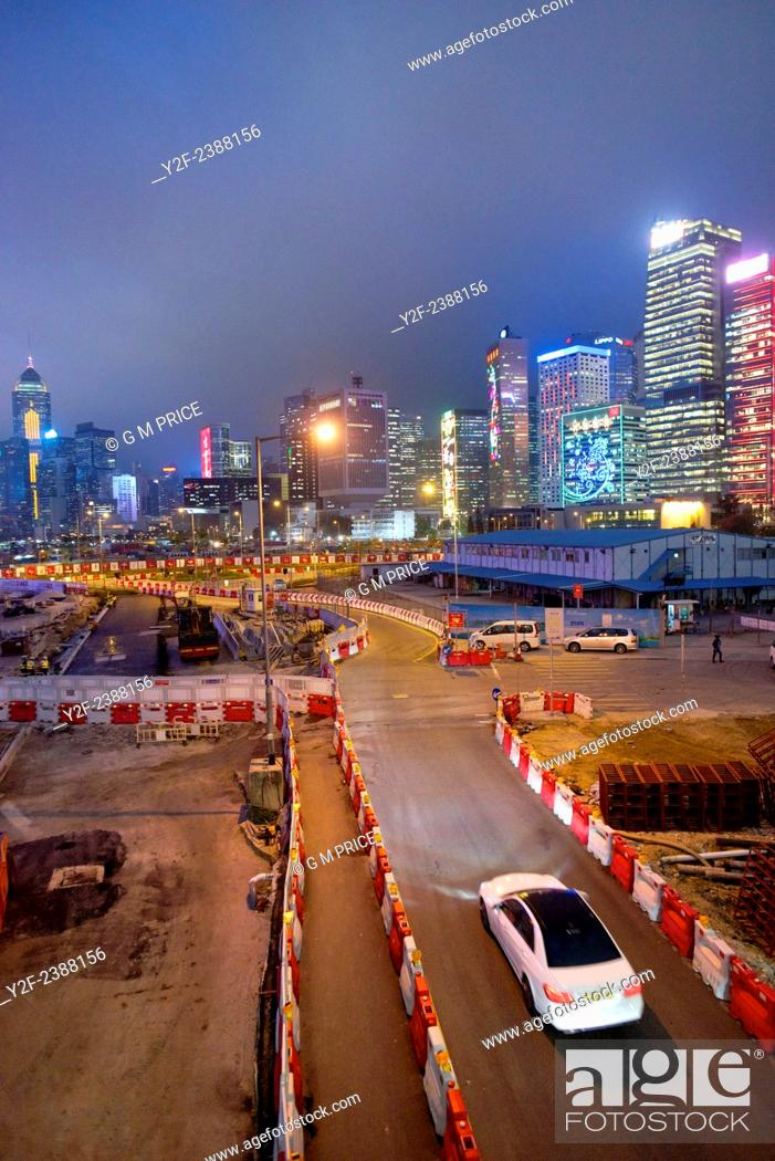 Stock Photo: a white car drives along temporary construction site road with Hong Kong skyline in the background.