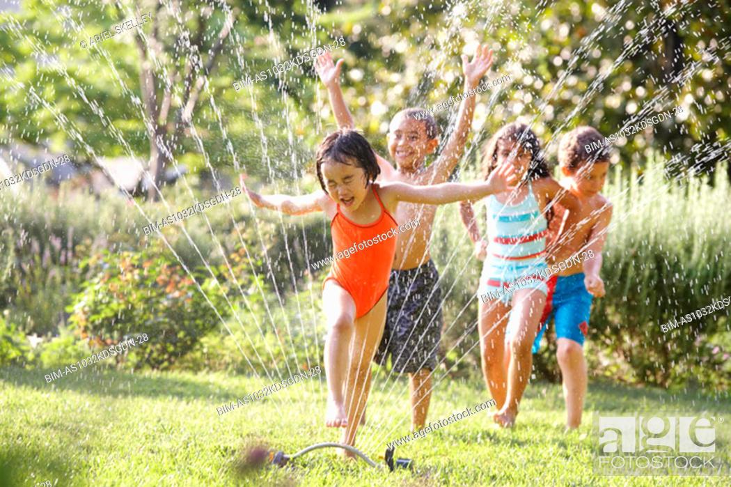 Stock Photo: Children running through water sprinkler.