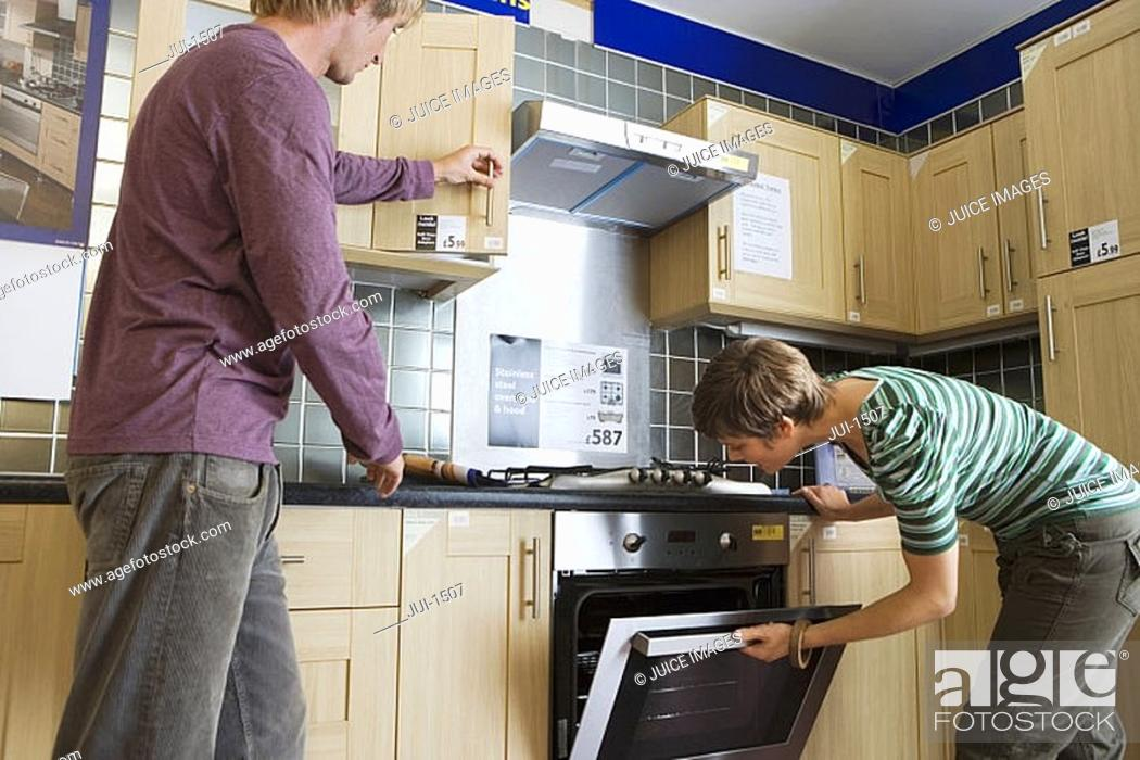 Stock Photo: Couple looking at new kitchen in home furnishings store, man opening cupboard, woman checking oven.