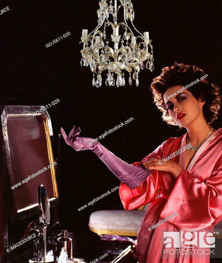 Stock Photo: Young woman putting on satin glove.