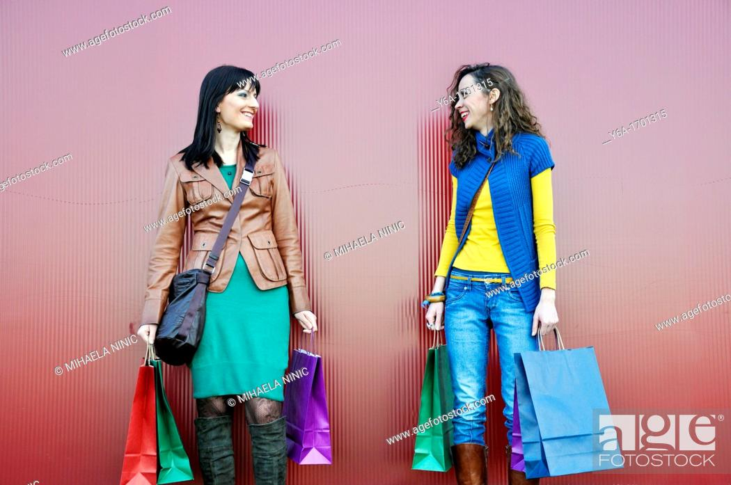 Stock Photo: Two young women outdoors with shopping bags.