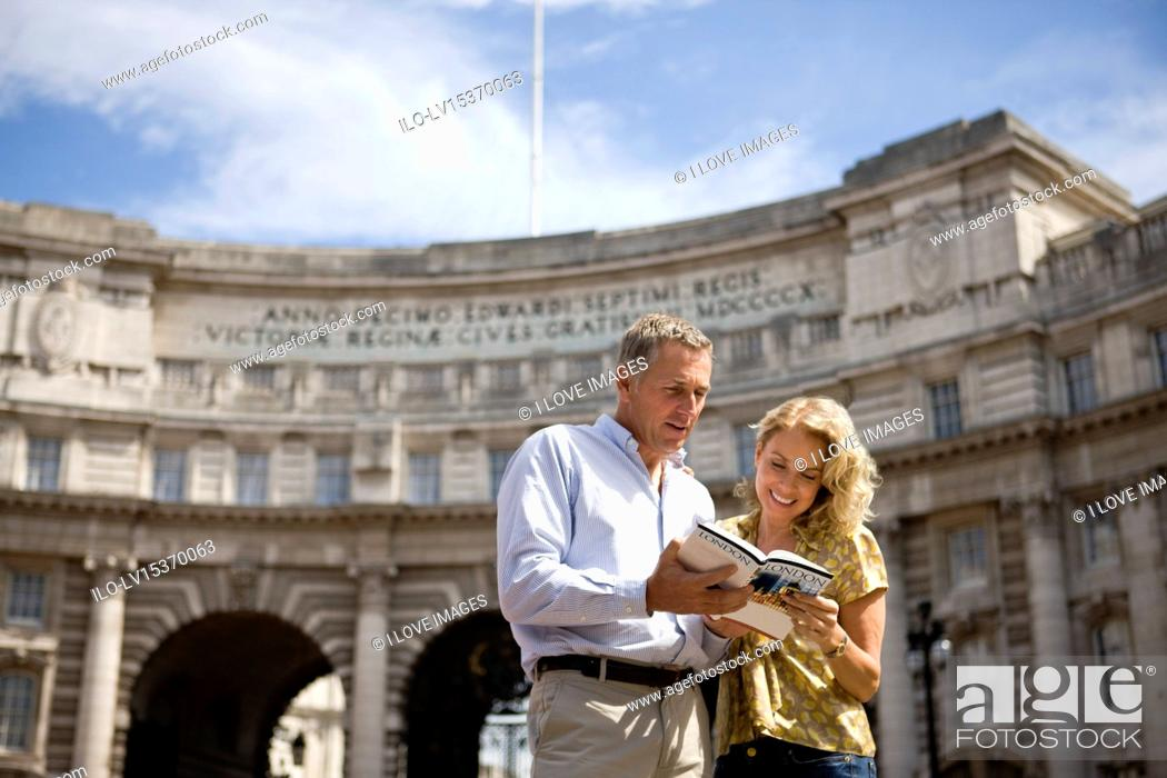 Stock Photo: A middle-aged couple standing in front of Admiralty Arch, looking at a guidebook.