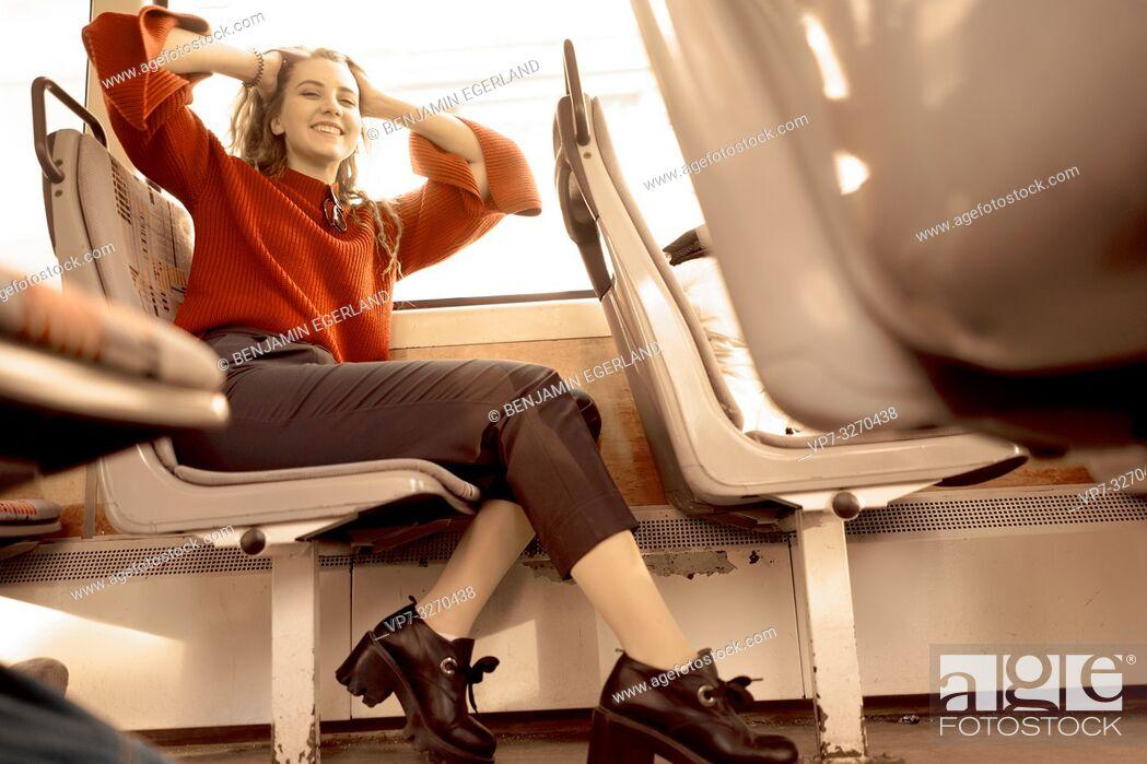Imagen: young happy woman sitting in public transport, in city Cottbus, Brandenburg, Germany.