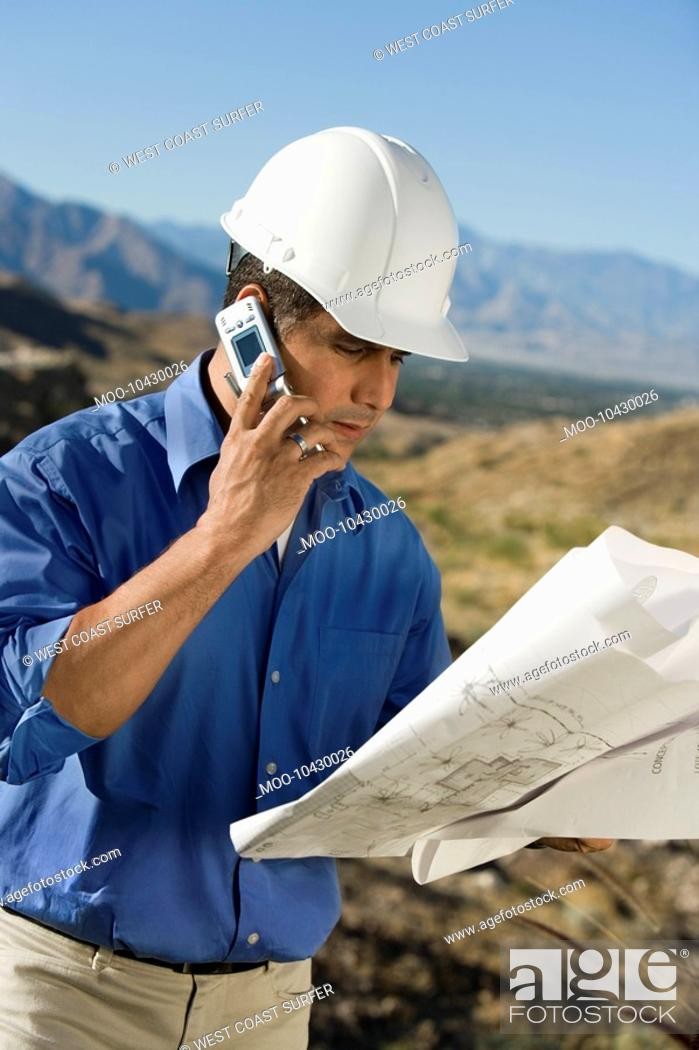 Stock Photo: Construction worker using mobile phone portrait.
