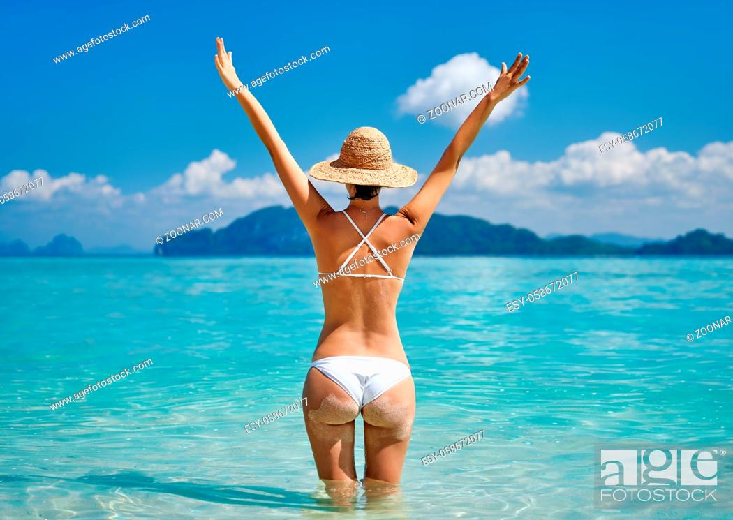 Stock Photo: Rear view of a beautiful happy girl with raised hands enjoy her tropical beach vacation. Summer relax, travel destination.