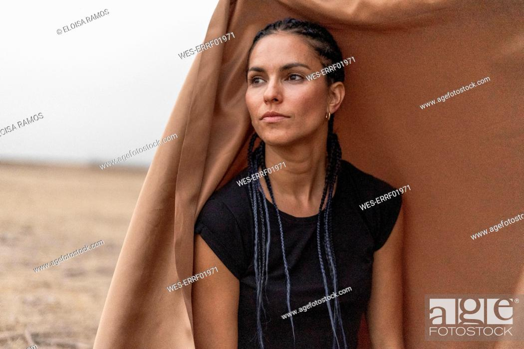 Stock Photo: Portrait of woman in bleak landscape looking at distance.