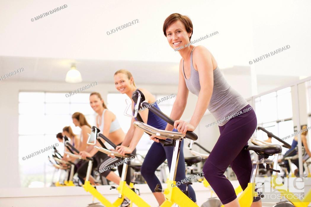 Stock Photo: Portrait of smiling women on exercise bikes in gymnasium.