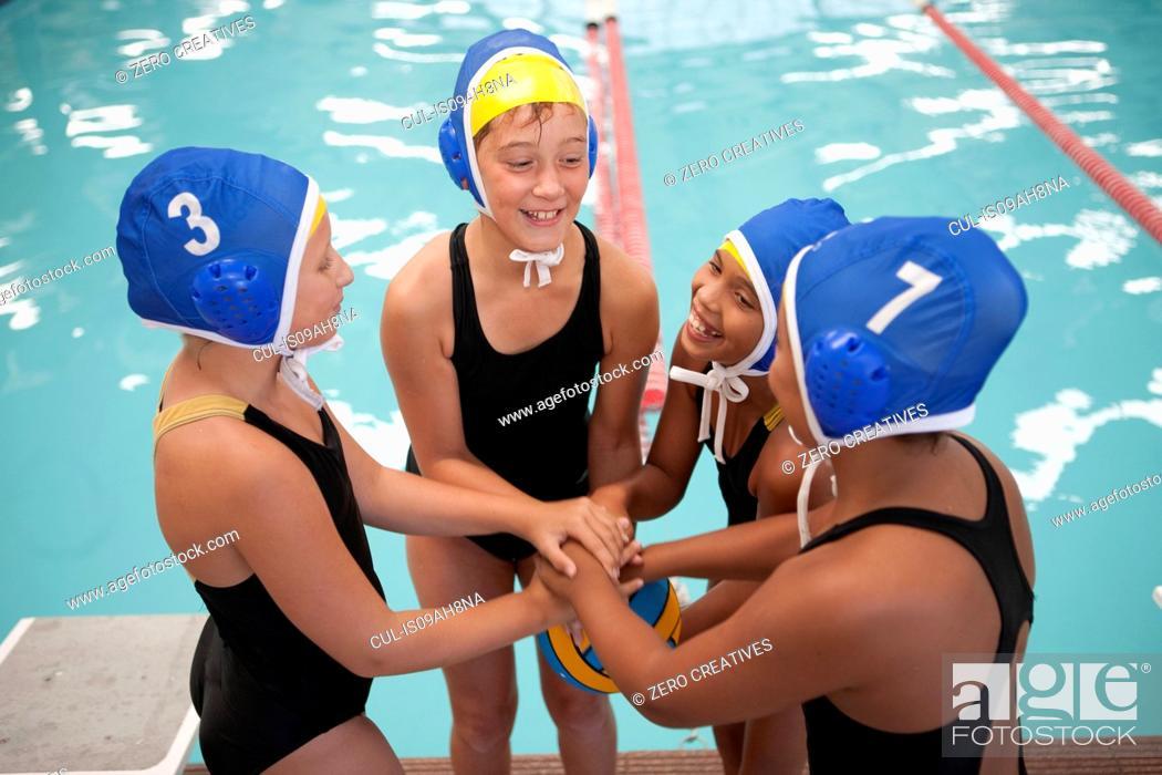 Imagen: Four schoolgirl water polo players holding hands poolside.