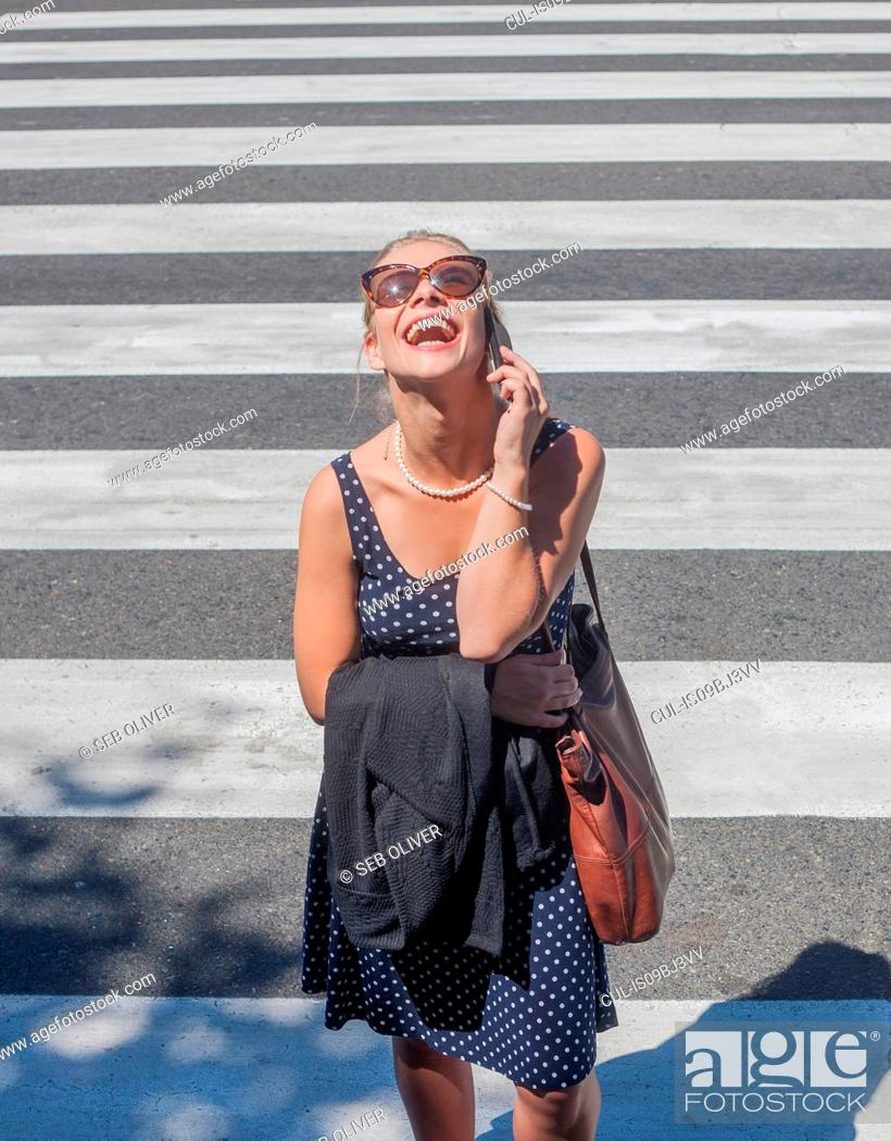 Stock Photo: Young woman laughing on mobile phone on zebra crossing.