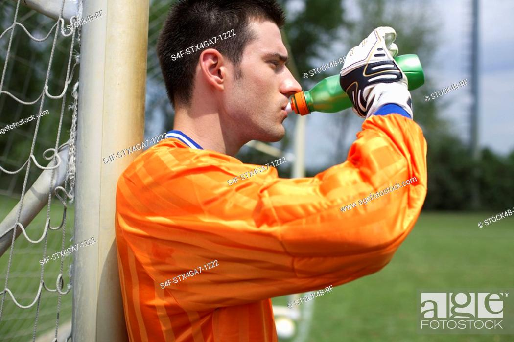 Stock Photo: Goalkeeper leaning against goal while drinking.