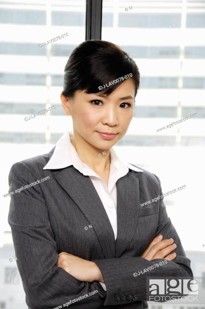 Stock Photo: Businesswoman standing with her arms crossed.