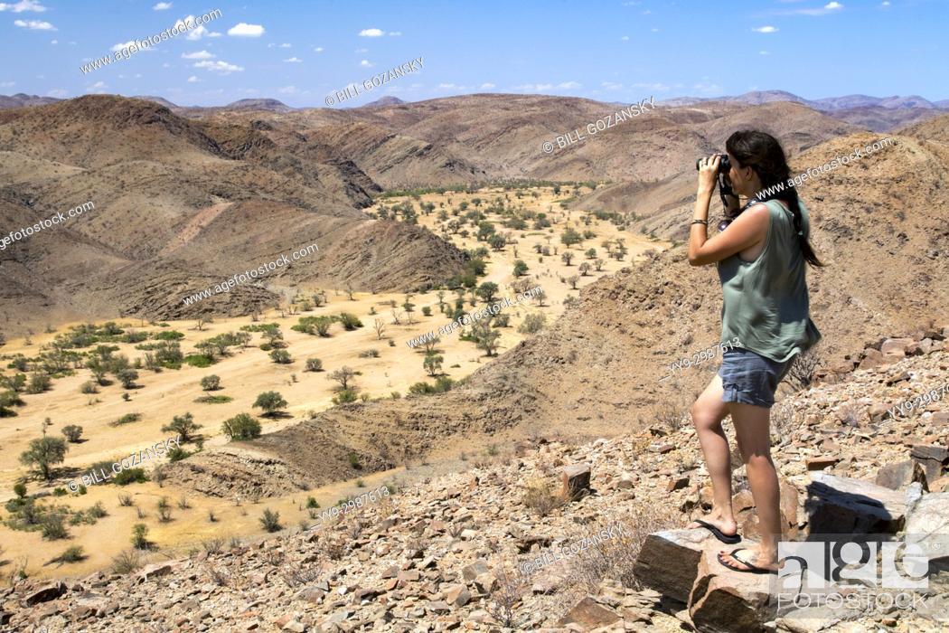 Stock Photo: Woman overlooking Huab River in Damaraland - Huab Under Canvas, Damaraland, Namibia, Africa.