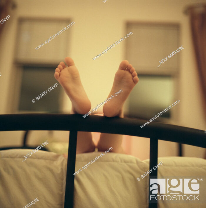 Stock Photo: Feet resting on bed frame.